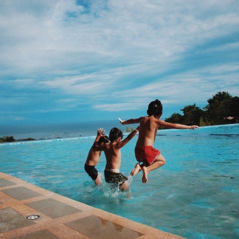 Barn hopper ut i bassenget.