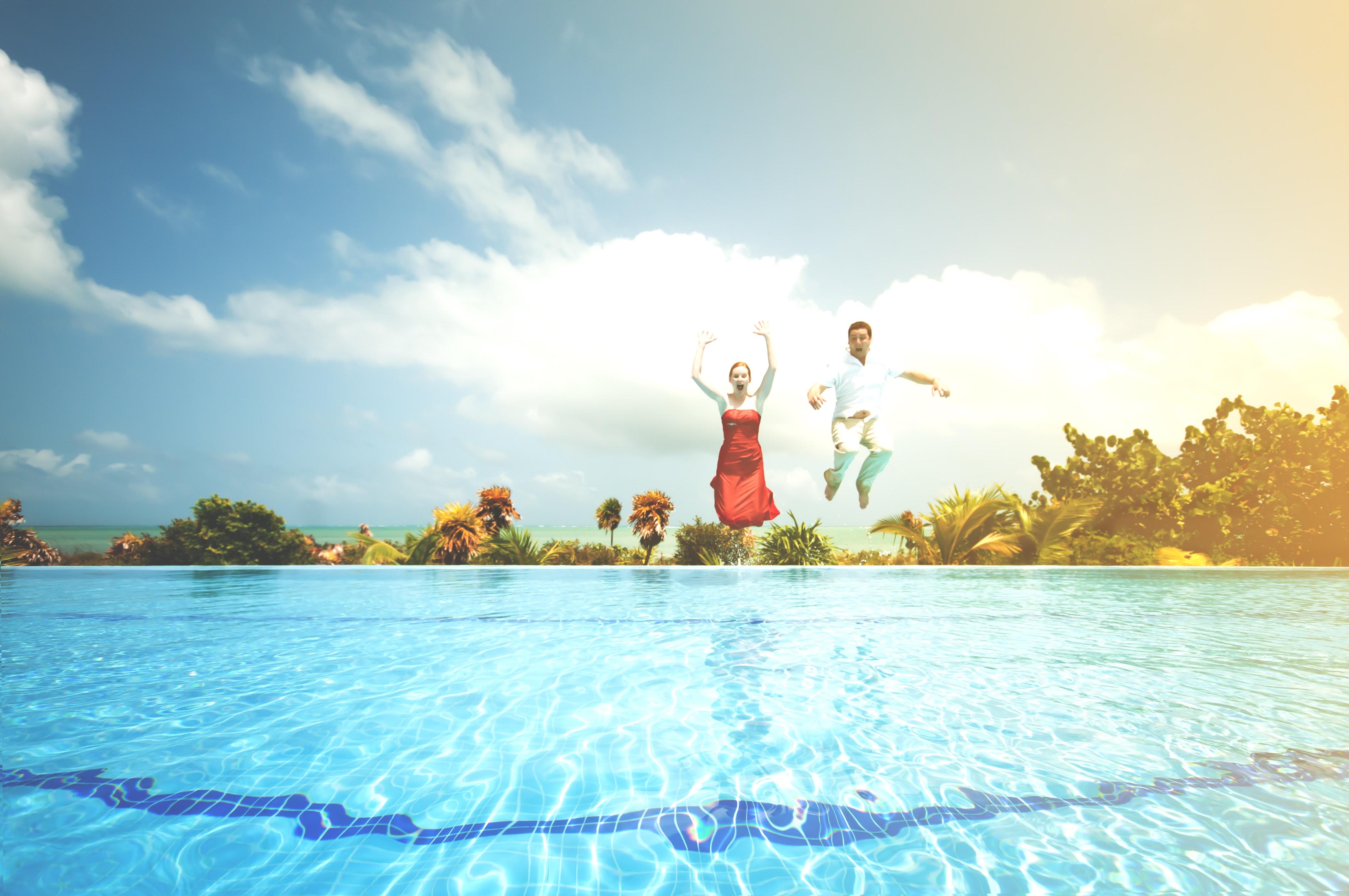 Voksne hopper ut i bassenget.